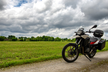 motorcycle on a path with a cloudy sky Fototapete