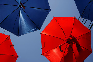 A worker arranges coloured umbrellas hanging over a street in preparation for a music festival at the weekend, in Zabbar