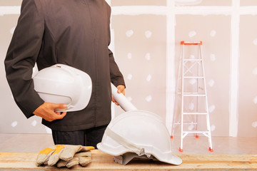 engineering businessman holding helmet white in the work gypsum board wall interior decoration of home in construction site