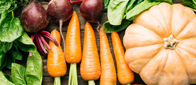 carrots, beets, spinach, pumpkin on a wooden background, fresh vegetables, banner