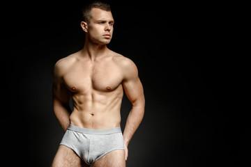 Guy in grey underwear on black background