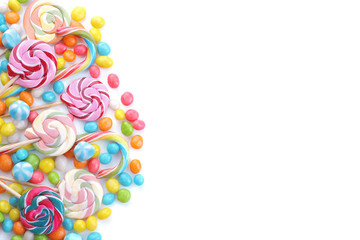 Multicolored lollipops and round candies on a white background. Top view. Isolated.