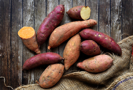 Mix of sweet potatoes with sack over wooden background