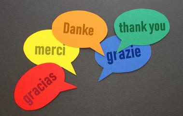 """""""Danke"""" in den wichtigsten Sprachen Europas in Sprechblasen auf dem Tisch"""