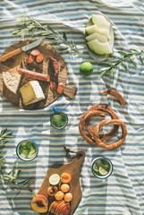 Aluminium Prints Picnic Flat-lay of summer picnic set with fruit, cheese, sausage, bagels and lemonade over striped blanket, top view, vertical