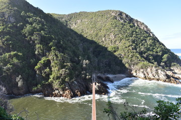 Mountainous Landscape with the beautiful beach and the famous Storms River Bridge at Tsitsikamma National Park in South Africa