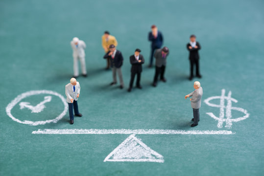 business miniature people on chalk balance time and money bar background
