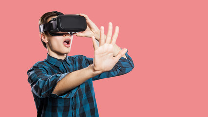 Young man with vr headset on pink background.