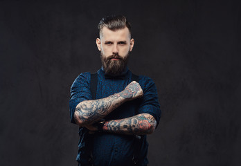 Portrait of a handsome old-fashioned hipster in a blue shirt and suspenders, standing with crossed arms in a studio.