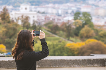 Young girl taking photos of Old Town in European city Prague.