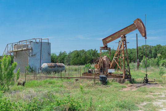 Rustic working pump jack pumping crude oil out of well to tank. Pumper and water emulsion at oil drilling site in Gainesville, Texas, US. Old pump jack, oil tanks for Energy and Industrial background