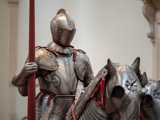 Exhibition of 15th century German plate armor around the time of late Middle Ages. The knight holds a land in his right arm while mounted on a heavily armored horse.