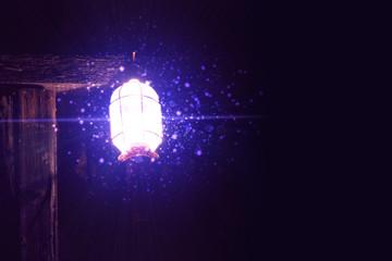 magic glow of the lantern on a dark background