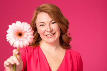 Beautiful happy woman with gerbera flower in hands on a pink background.