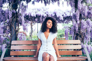 Young black woman sitting surrounded by flowers