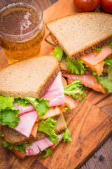 sandwiches with ham and smoked salmon with beer glasses