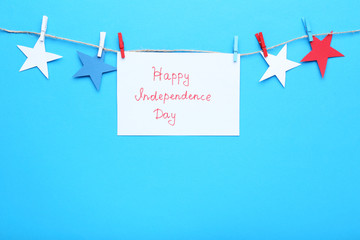 Paper stars and inscription Happy Independence Day on blue background