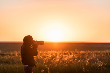 Young male photographer shoots sunset in field