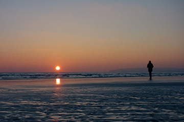 Person in silhouette on a beach at sunset