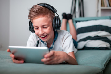 Teenage boy using tablet with headphones lying on bed in his room