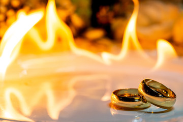 Gold Wedding Rings on White Plate with Fire in the Background with Party Decorations