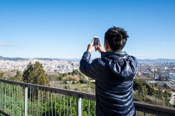 Traveler man photographing city and sea with mobile phone