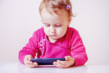 Little beautiful child girl using smartphone as symbol of work or study.