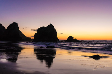 Reflections of giant rocks in the wet sand at sunset at the Praia da Ursa, Portugal