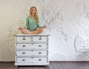 Young woman meditating sitting on a vintage dresser.