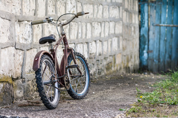 Old rusty children's bike near a blue door in the garden