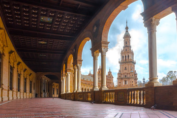 Famous Plaza de Espana hallway in Seville, Spain. Filled in a soft light with the tower in the background. Pigeons walking by with no one else around.