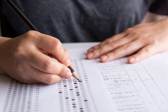 Exam. Students holding pencil writing selected choice on answer sheets and Mathematics question sheets. students testing doing examination. school exam