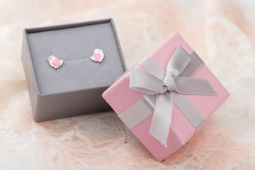 Small pink and gray jewelry gift box with bow on lace background