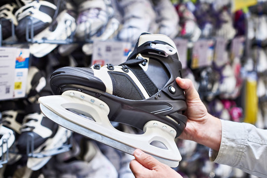 Hands of man with hockey skates in sports shop