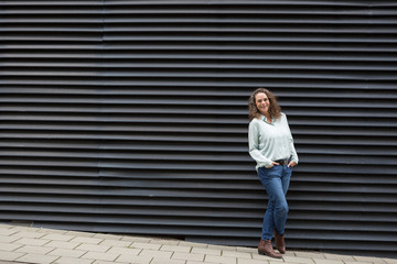 Trendy jaunty mature woman in jeans posing with crossed legs and hands in pockets front of a black ridged wall in town with copy space
