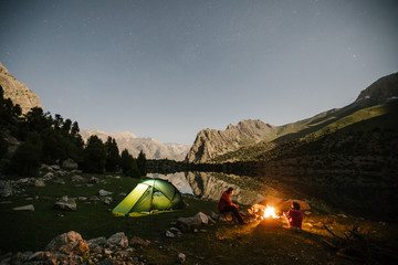 couple sitting beside a campfire on a mountain lake at night with an illuminated green tent