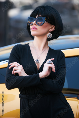 Beautiful brunette woman with yellow sport car. Young woman with dark hair  in black bodysuit e00efff85