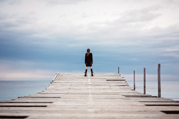 Young girl on a bridge by the seaside