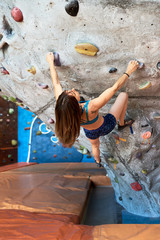 Climbing sportswoman on upright wall.