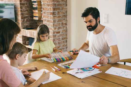 Caucasian Family of Four Coloring and Drawing Together at Kitchen Table