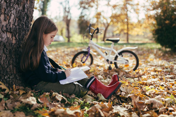 Young girl studying in the park.