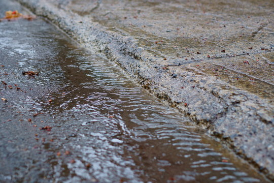 In a rainy day, water flows along the sidewalk. Narrow focus.
