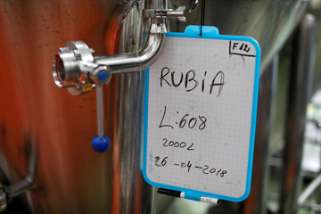 A sign indicating the type of a beer hangs on a vat at the Cibeles microbrewery in Leganes, near Madrid