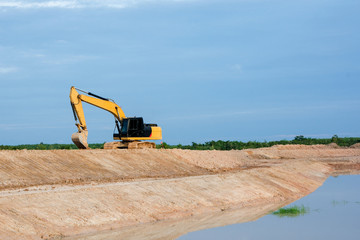 Yellow excavator machine working earth moving works riverside at construction site