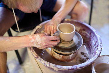 Man making a pot of clay. Pottery wheel. Workshop of art therapy. A dirty male hands. Modeling of a ceramic cup