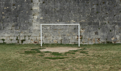 Soccer goal in front of old wall