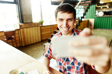 Relaxed casual man taking selfie using smartphone and sitting at table in light