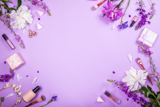 Set of cosmetics, brushes and jewellery with fresh flowers on purple background. Summer sale. Shopping