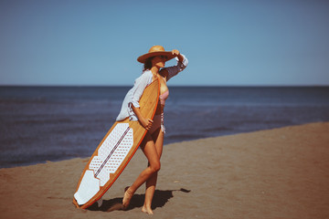 Young woman with a surf board on the beach