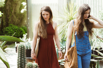Two young women exploring a greenhouse together.